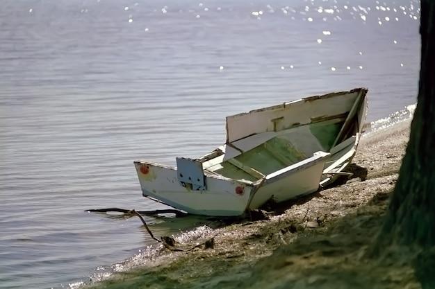 Gebrochenes kleines boot auf dem gewässer geparkt