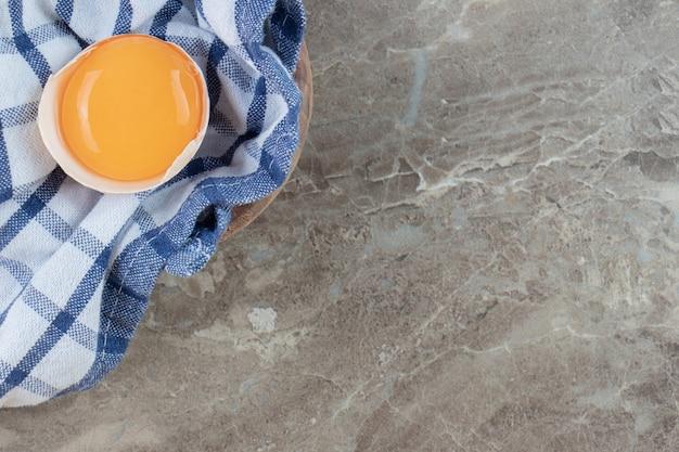 Gebrochenes rohes ei auf marmoroberfläche mit einem tuch