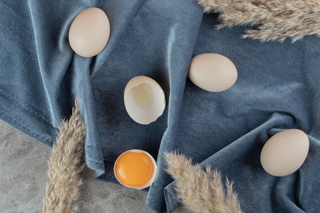 Gebrochenes rohes ei auf marmoroberfläche mit stoff