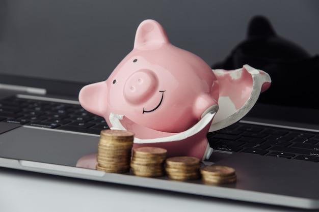 Gebrochenes rosa sparschwein und stapel von münzen auf einem laptop