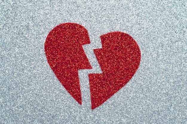 Gebrochenes rotes herz auf grauem glitzerpapier, ein trennungskonzept. lametta-applikation. ein symbol für liebe, valentinstag, romantische gefühle und emotionen.
