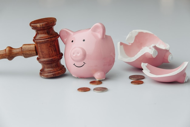 Gebrochenes schweinchen mit münzen und holzhammer. geschäfts- und insolvenzkonzept