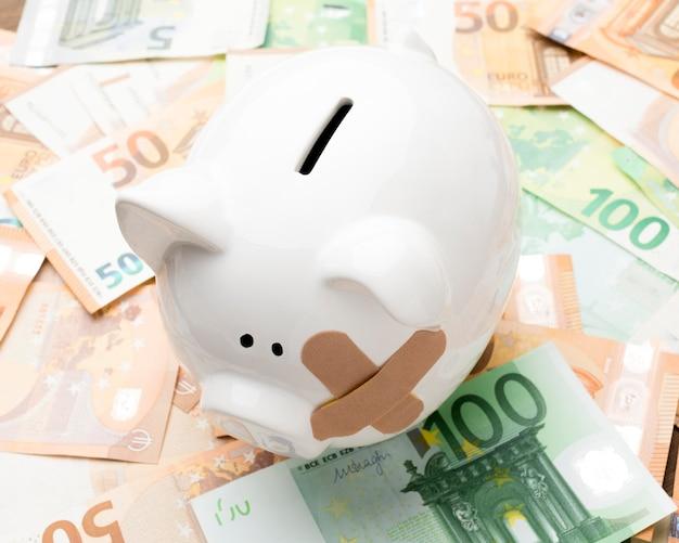 Gebrochenes sparschwein, das auf geld steht