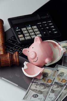 Gebrochenes sparschwein, dollarnoten und hammer auf der tastatur. auktions- und insolvenzkonzept. vertikales bild