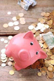 Gebrochenes sparschwein mit bargeld und münzen auf holz