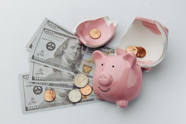 Gebrochenes sparschwein mit dollarnoten auf weißem hintergrund