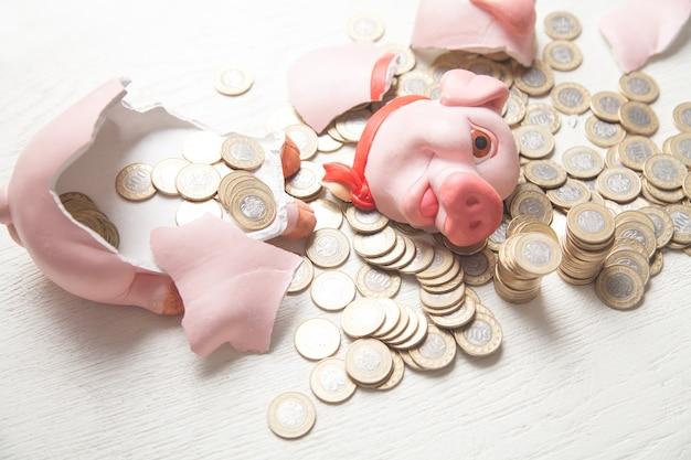 Gebrochenes sparschwein mit münzen auf dem weißen tisch