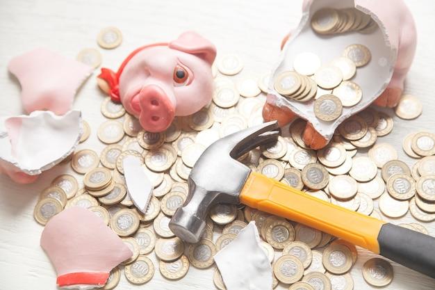 Gebrochenes sparschwein mit münzen auf der weißen oberfläche.