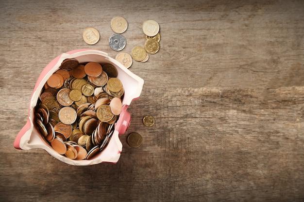 Gebrochenes sparschwein mit münzen auf hölzernem hintergrund
