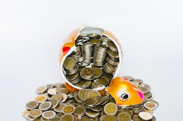 Gebrochenes sparschwein mit thailändischen baht-münzen auf weißem hintergrund.