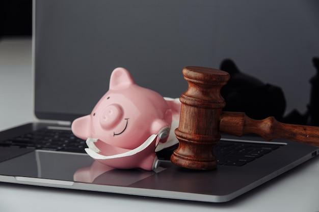 Gebrochenes sparschwein und hölzerner richterhammer auf laptop. auktions- und insolvenzkonzept