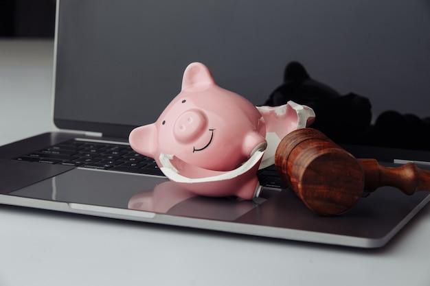 Gebrochenes sparschwein und hölzerner richterhammer auf laptop. geschäfts-, finanz- und insolvenzkonzept.