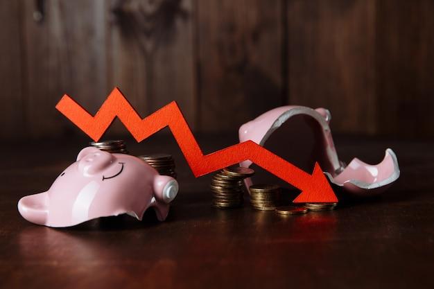 Gebrochenes sparschwein und roter pfeil mit münzenstapel