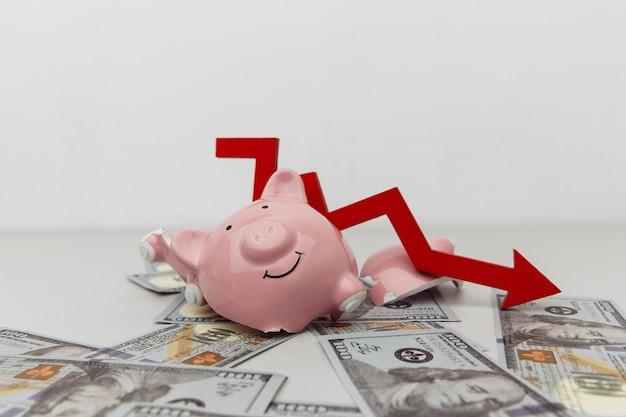 Gebrochenes sparschwein und roter pfeil nach unten mit dollarbanknoten, die auf weißem investitions- und konkurskonzept isoliert werden