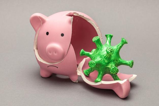 Gebrochenes sparschwein und virus. geldkrisenkonzept aus epidemie oder quarantäne. grauer hintergrund.