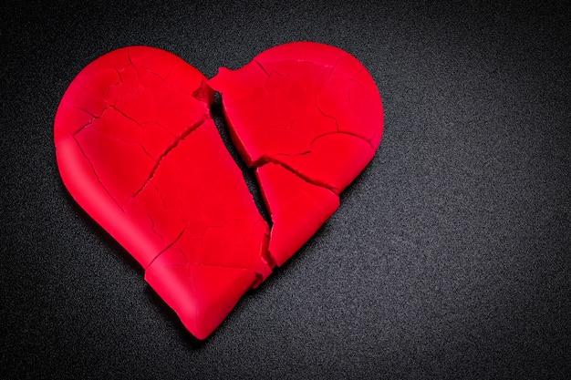 Gebrochenes und gebrochenes rotes herz auf einem schwarzen hintergrund. nahansicht. vignette. valentinstag.