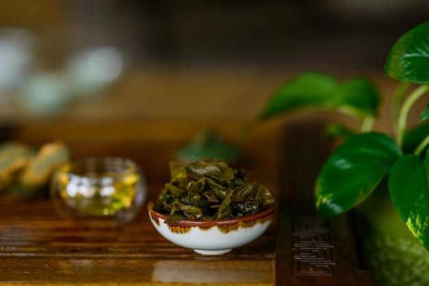 Gebrühte blätter des chinesischen oolong-tees in einer tasse auf einem tee-holzbrett. tee-zeremonie.