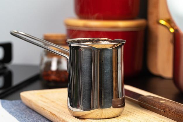 Gebrühter kaffee in einer metalltürke auf einer küchentheke nah oben