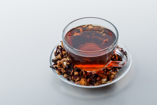 Gebrühter tee in einer tasse mit getrockneten kräutern und früchten