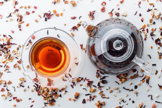 Gebrühter tee in teekanne und tasse mit gemischten getrockneten kräutern draufsicht auf einer weißen oberfläche