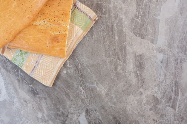 Gebündelte brote von halb geschnittenem tandoori-brot auf marmor.