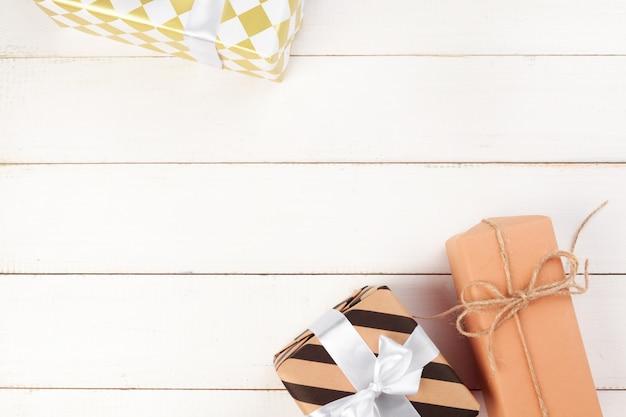 Gebundene bogengeschenkboxen auf weißem hölzernem hintergrund, draufsicht
