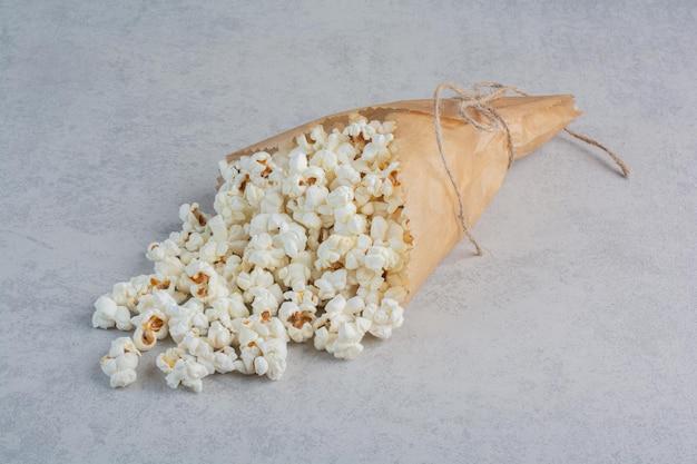 Gebundene papierverpackung gefüllt mit popcorn auf marmoroberfläche