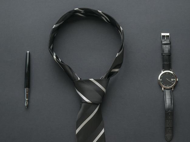 Gebundene schwarze und weiße herrenkrawatte, stift und uhr auf schwarzem hintergrund. themen für männer.