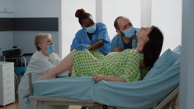 Geburtshelfer und afroamerikanische krankenschwester, die baby zur welt bringt