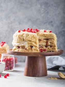 Geburtstag cremige torte napoleon oder gehackter kuchen. konditor verziert mit beeren auf einem backblech, köstliche süße. das konzept des selbst gemachten gebäcks, torte kochend.