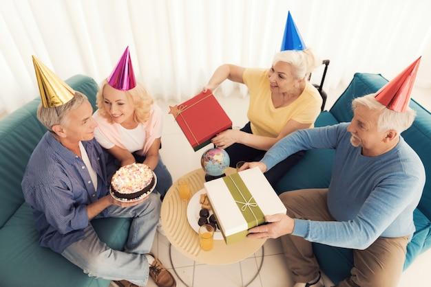 Geburtstag der älteren person. leute in hüten eines geburtstages.