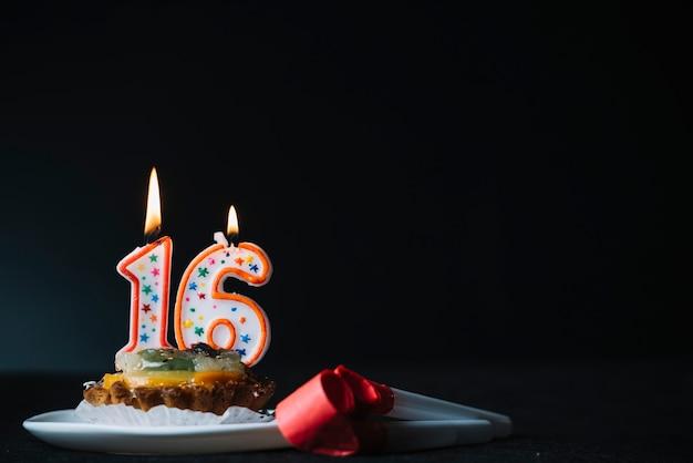 Geburtstag der nr. 16 beleuchtete kerze auf der scheibe des törtchen- und parteihorngebläses gegen schwarzen hintergrund