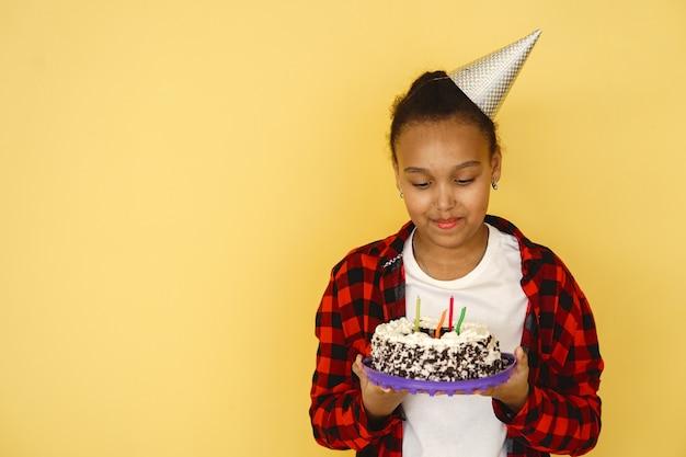 Geburtstag des kleinen mädchens lokalisiert auf gelber wand. kind, das kuchen hält.