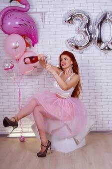 Geburtstag eines mädchens in einem rosa kleid mit luftballons und einem kuchen 30 jahre alt