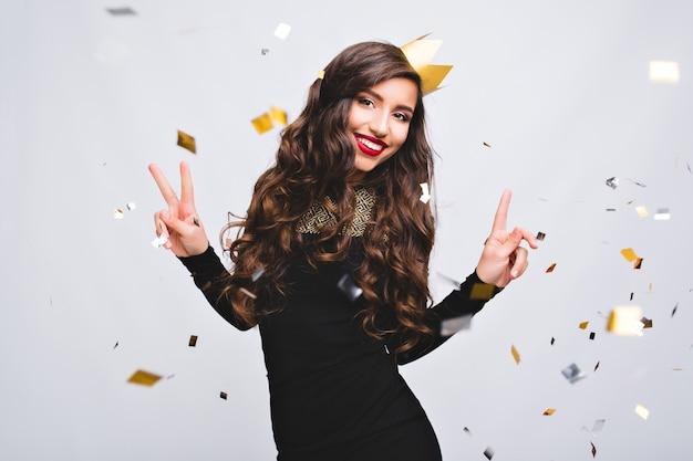 Geburtstag, helle gefühle, nachtparty der freudigen hübschen frau. sie trägt ein schwarzes luxuskleid und eine gelbe krone. funkelndes konfetti, tanzen, festtage, spaß haben, lächeln.