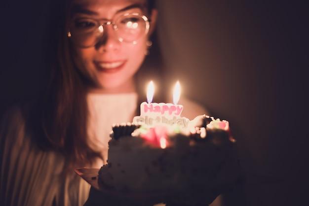 Geburtstag. mädchen mit einem kuchen mit kerzen, halteplatte der jungen frau mit geschmackvollem geburtstagskuchen