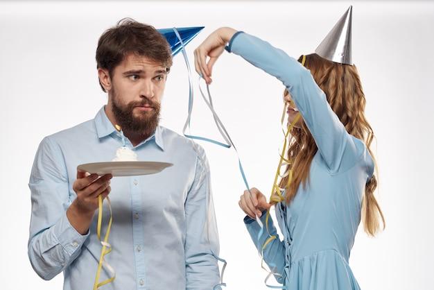 Geburtstag mann und frau mit einem cupcake und einer kerze in einem partyhut