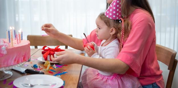 Geburtstag mutter und kind sitzen am festlichen tisch, zündet kerzen auf dem kuchen. urlaubskonzept