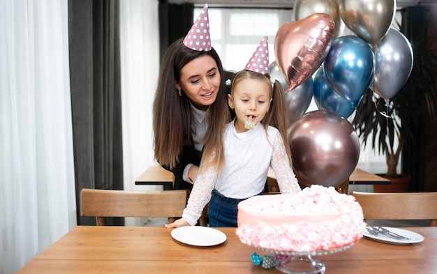 Geburtstag mutter und tochter in hüten feiern auf dem tisch einen festlichen kuchen und luftballons.