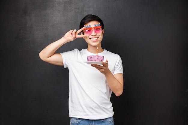 Geburtstags-, feier- und partykonzept. porträt des glücklichen freundlichen lächelnden asiatischen mannes, der b-tag genießt, tragen lustige brille halten kuchen mit brennender kerze, wunsch machen, zeigen friedenszeichen nahe auge