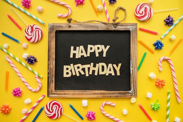 Geburtstags-komposition mit kerzen, süßigkeiten und schiefer