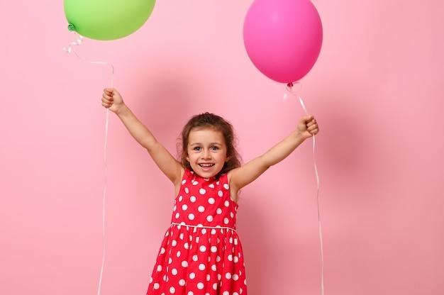 Geburtstagsbaby in rosa kleid mit tupfenmuster gekleidet, das ihre arme mit bunten luftballons in den händen hebt, lächelnd in die kamera schaut, einzeln auf rosafarbenem hintergrund mit kopierraum
