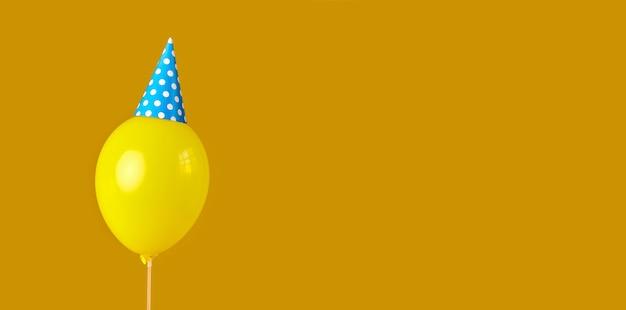 Geburtstagsballon mit partyhut auf orangem hintergrund