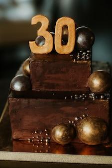 Geburtstagschokoladenkuchen mit einer zahl dreißig. verziert mit goldenen schokoladenkugeln