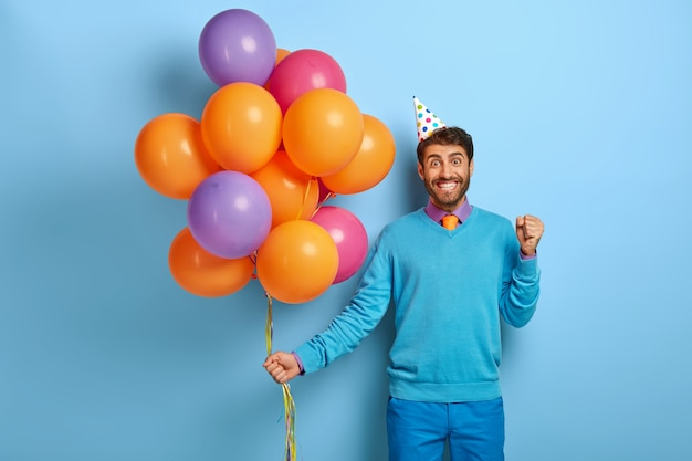 Geburtstagsfeier-konzept. positiver mann ballt vor glück die fäuste