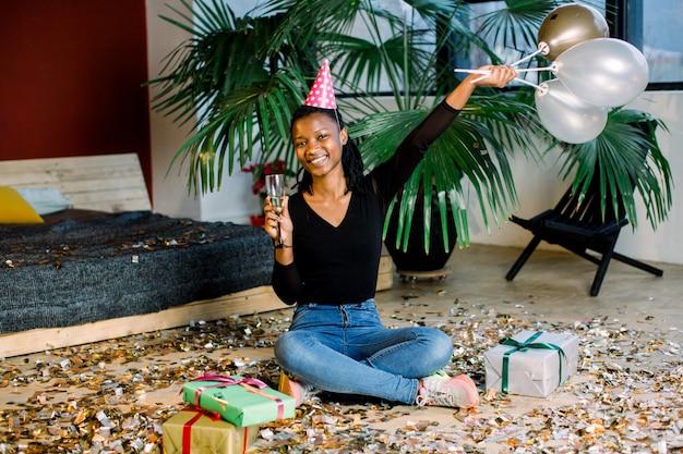 Geburtstagsfeier, neujahrskarneval. junge afrikanische lächelnde frau, die helles ereignis feiert ,. funkelndes konfetti, spaß haben, tanzen und champagner trinken