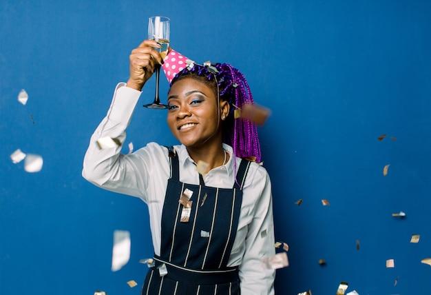 Geburtstagsfeier, neujahrskarneval. junge lächelnde afrikanische frau auf blauem raum, der helles ereignis feiert, trägt elegante modekleidung und rosa partyhut. funkelndes konfetti, spaß haben, tanzen