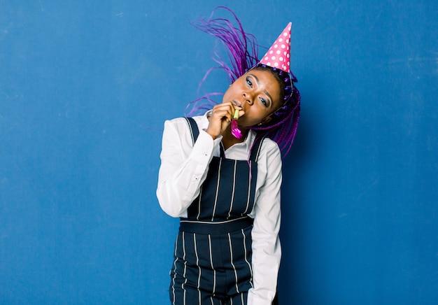 Geburtstagsfeier, neujahrskarneval. junge lächelnde afrikanische frau auf blauem raum, der helles ereignis feiert, trägt eleganten weißen moderock und schwarze hose, mit rosa partyhut mit krachmacher.