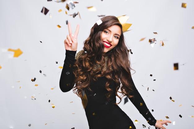 Geburtstagsfeier, neujahrskarneval. junge lächelnde frau, die helles ereignis feiert, trägt elegantes schwarzes modekleid und gelbe krone. funkelndes konfetti, spaß haben, tanzen.
