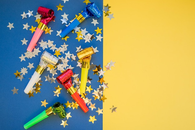 Geburtstagsfeier pfeift auf farbigem hintergrund. buntes feiermuster mit partygebläsehörnern